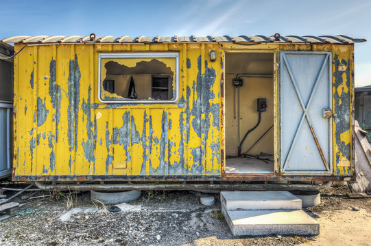 Dilapidated yellow worksite hut