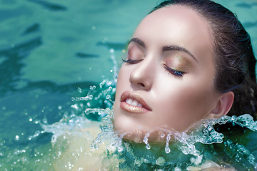 Wet woman face with water drop. Moisturizing in the sea