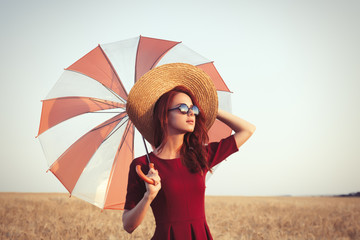 Girl in red dress with umbrella and hat