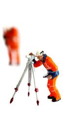 Miniature construction workers. Miniature scale model construction workers isolated on white background.
