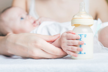 Baby holding a baby bottle with breast milk