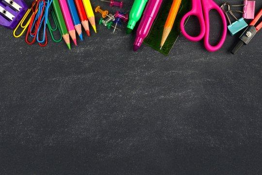 School supplies top border on a chalkboard background