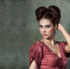 Attractive young lady in pink dress and funny styling posing on
