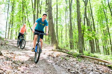 Paar auf Mountainbike Fahrrad am Berg im Wald