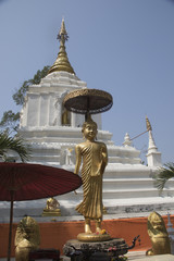 Statue of the Buddha with umbrella in front of small chedi.Chiang Mai,Thailand