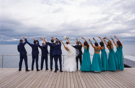 Guests on the wedding celebration are holding their hands up wit