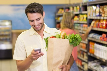 Smiling handsome man buying food and using his smartphone