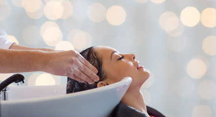 happy young woman having salon hair wash