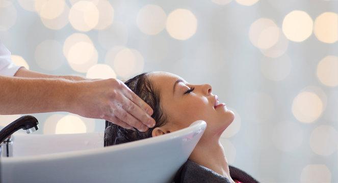 happy young woman having salon hair wash