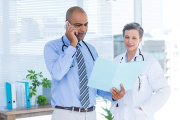 Concentrated doctor showing file to his colleague while calling