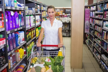 Portrait of smiling woman walking in aisle with his trollet