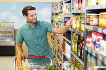 Smiling man taking a oil in the aisle