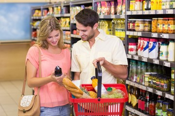 Smiling bright couple buying food porducts with shopping basket
