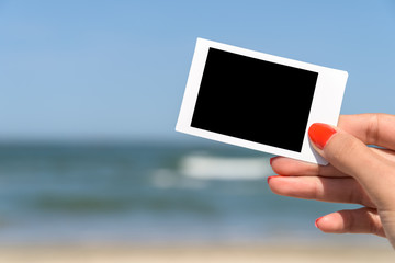 Girl Hand Holding Blank Instant Photo Card On Beach In Summer