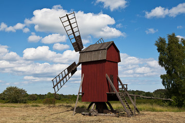 rote Bockwindmühle vor weiß-blauem Himmel