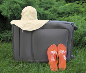 suitcase, sun hat, flip flops orange closeup on green background