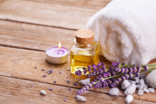 Spa still life with lavender oil, white towel and perfumed candle on natural wood