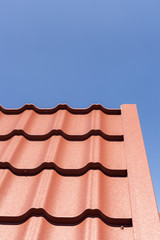 Red metal tile against blue sky