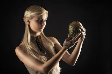 attractive woman in dress holding a dragon egg in hands