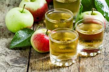 Cold apple juice and fresh apples on an old wooden table, select