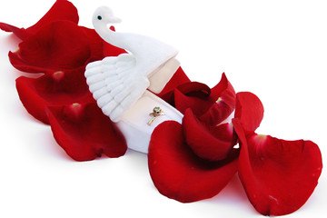 gold ring in a box in the form of a swan on red petals