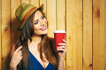 Woman Holding Coffee Cup. Yellow hat. Teeth smiling model