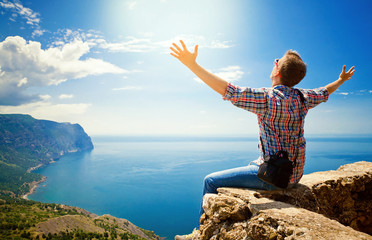 guy sitting on top of a mountain with arms outstretched