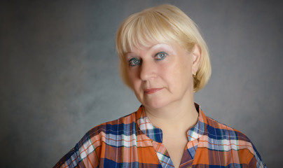 Portrait of middle aged woman on dark background.
