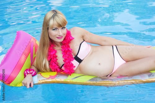 aa2bfdb611d5b Pregnant pretty girl is lying on mattress in swimming pool