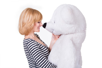 Beautiful young woman playing with big white teddy bear