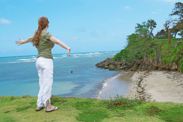 Woman On Ledge With Outstretched Arms Overlooking Ocean Scenery in the Dominican Republic