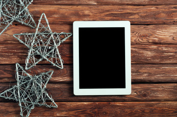 White tablet computer  on a wooden background with with Christmas stars. top view. copy space. free text space. close up