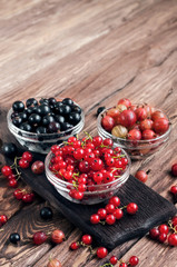 seasonal berries in a bowl on a wooden background. black currants, red currants, gooseberries. Copy space. free text space. close up