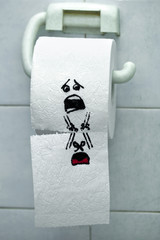 Roll of toilet paper and felt tip pen drawn funny faces