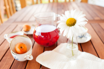 Fruit drink with flower on wooden table outdoors. Focus on flower. Healthy eating