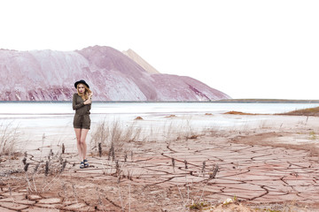 beautiful sexy cute girl in a fashion shot wearing a hat and overalls in the desert with dry cracked ground on a background of mountains on a summer day