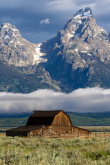 Iconic barn in Mormon Row with fog over the snake river and mountains in Grand Teton National Park in Wyoming