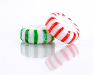 Red and Green Peppermint Candies on a Reflective White Background