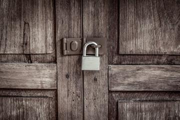 locked wooden door with silver padlock