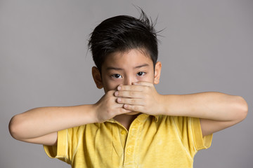 Young asian boy with both hands closing mouth