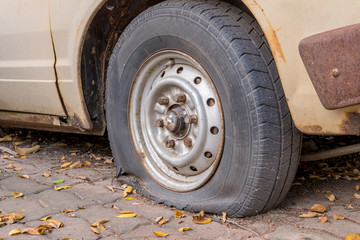 Deflated damaged tyre on car wheel
