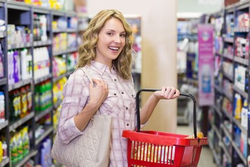 Portrait of a smiling pretty blonde woman buying a products