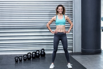 Standing muscular woman with hands on hips