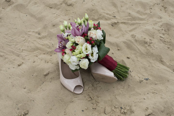 wedding bouquet and shoes in the sand
