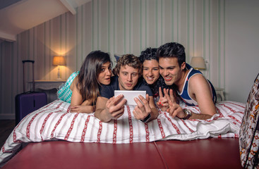 Young people taking a selfie lying over the bed