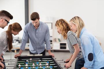 junge kollegen spielen kicker im büro