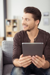lächelnder mann hält tablet in händen