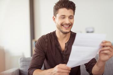 mann liest einen brief und lächelt