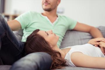 paar liegt entspannt auf dem sofa