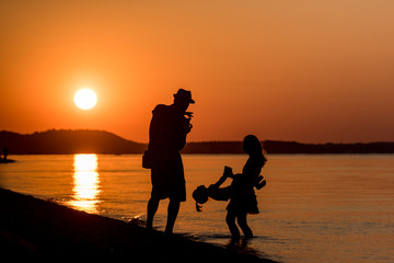 Family. Happy Young Family who Taking Photos on the Beach at Sunset.